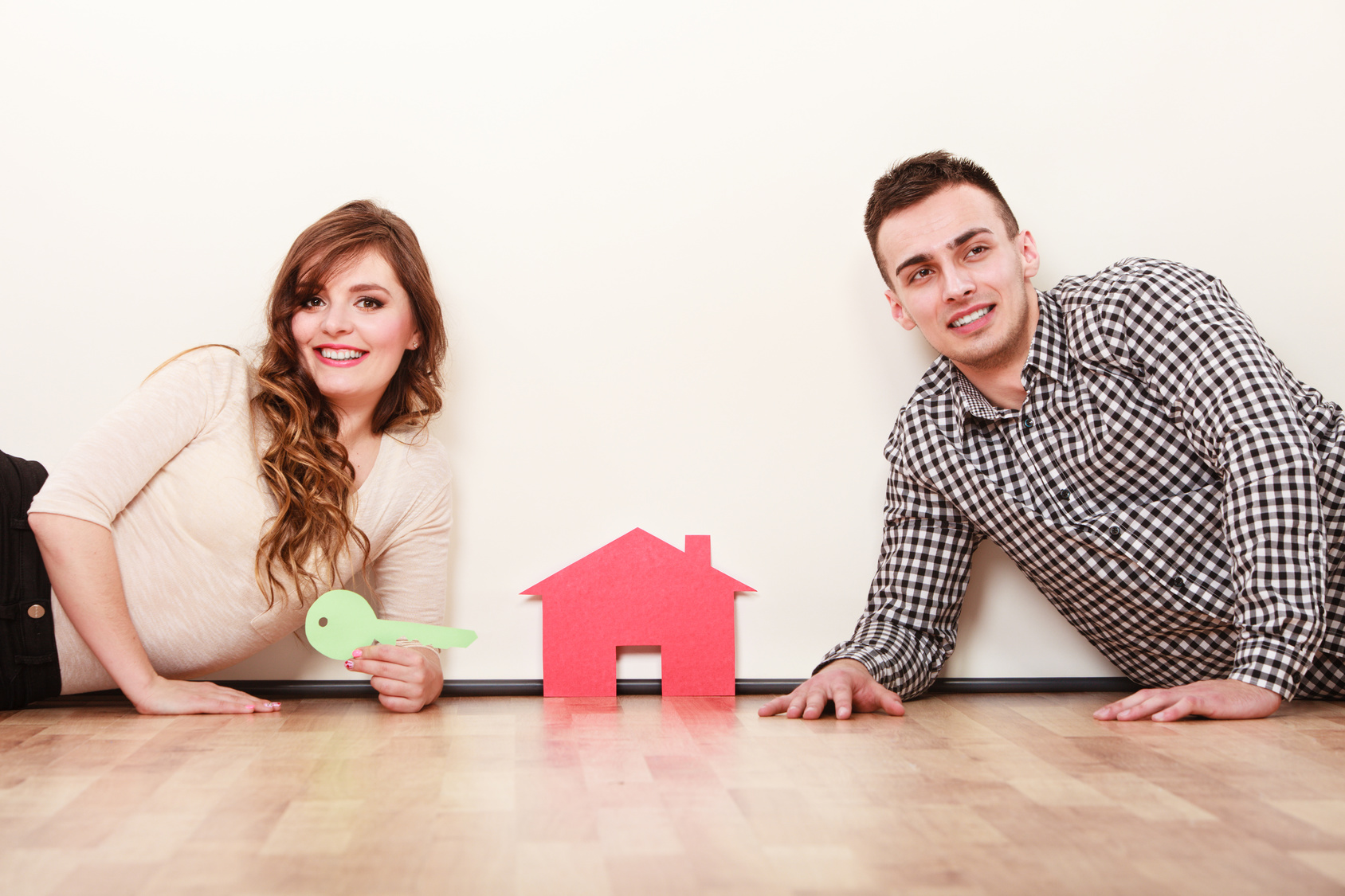 Smiling young couple laying on floor holding paper house and key. Husband and wife dreaming about new home. Housing and real estate concept.