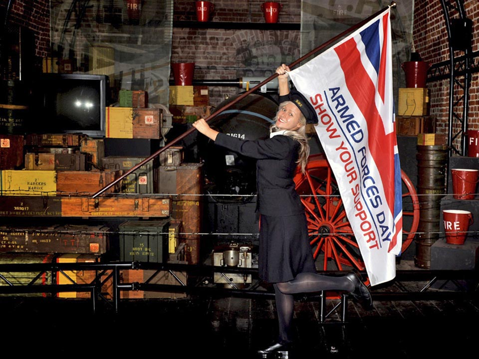 "Waving the flag for Armed Forces Day. Picture: LA(Phot) Alex Knott    In the name of nostalgia, Rebecca Richardson from Southampton but who works at St John C of E school in Gosport , agreed to help raise awareness of Armed Forces Day 2013. Rebecca agreed to raise awareness at the National Museum ""Explosion"" at Priddys Hard in Gosport whilst Dressed in a WW2 Wrens uniform which was kindly loaned the national Museum in HMNB Portsmouth, with additional loans from Sabre Sales in Southsea, Portsmouth.  Consent forms held at FRPU(East"
