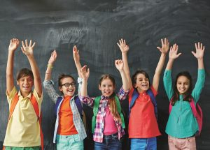 Schoolkids raising hands at chalkboard