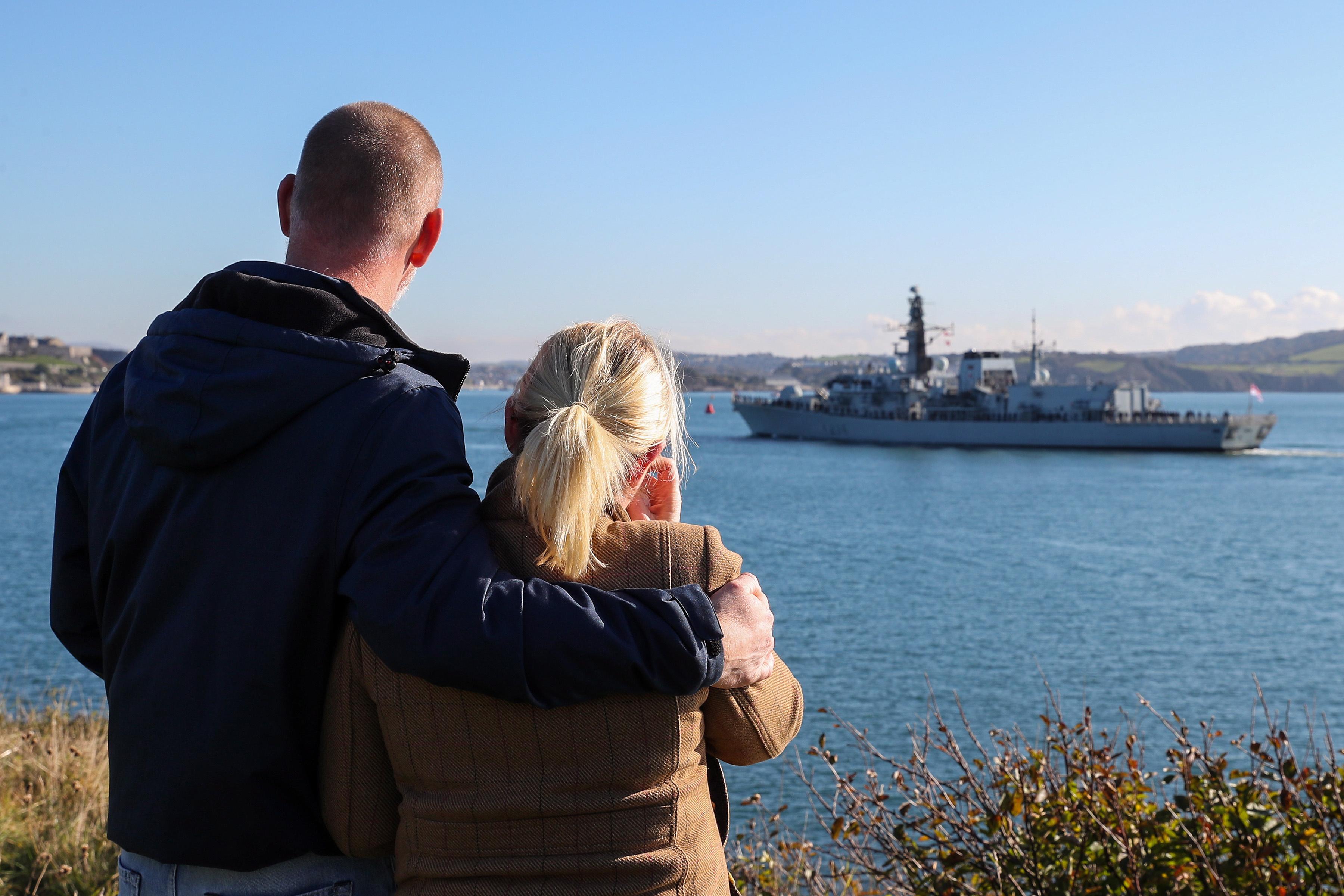 HMS Montrose departs Devonport, a couple looks on.