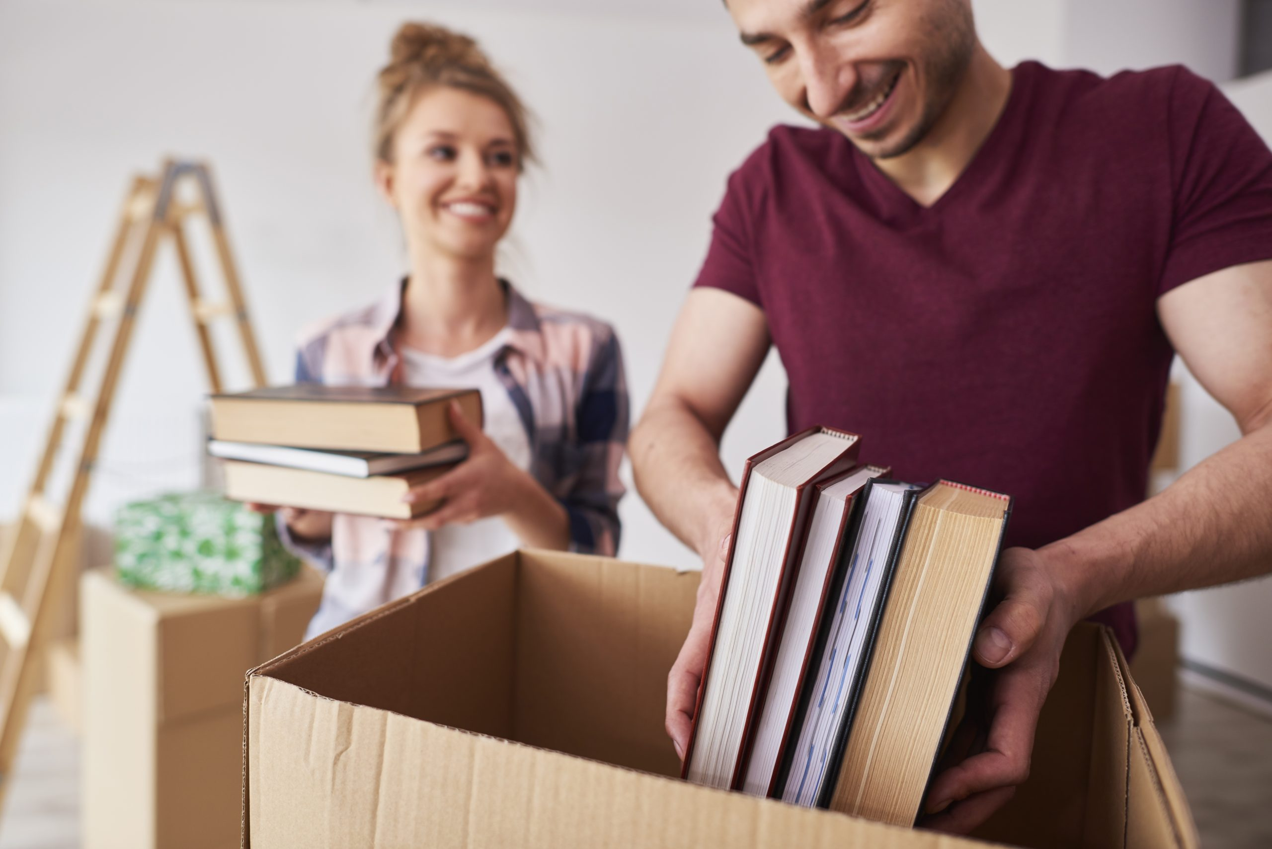 Young couple packing books into box