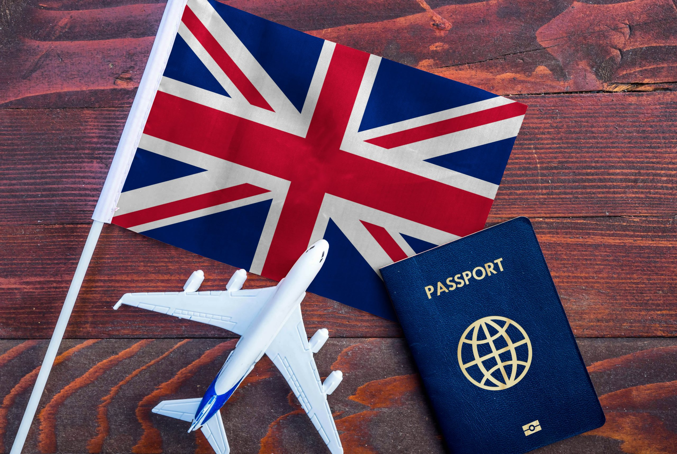 Flag of United Kingdom with passport and toy airplane on wooden background. Flight travel concept.